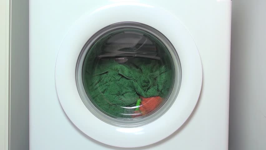 circular door of white washing machine running and turning with colored clothes