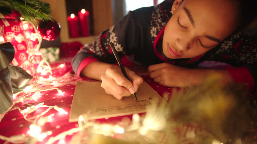 Teen girl is lying near decorated christmas tree and writing christmas letter to Santa Claus