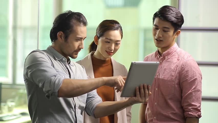 team of young asian business executives working together using digital tablet in office.