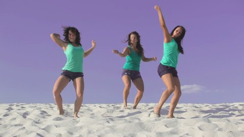 Beautiful women dancing on the sand together