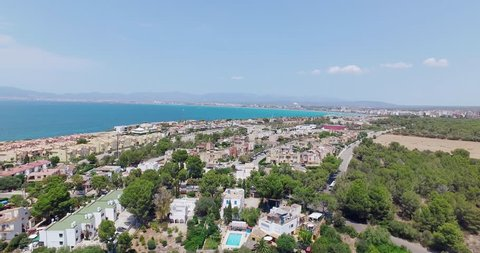 Drone flight at midday sun over Palma de Mallorca with pools and trees