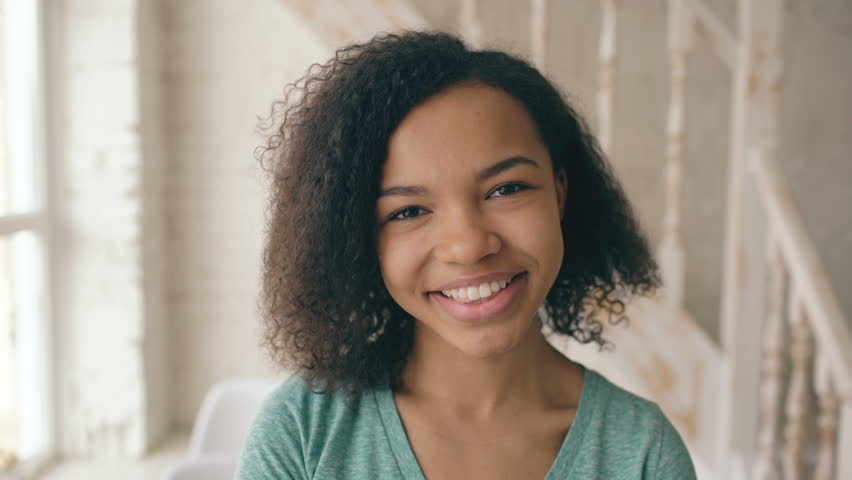 Closeup portrait of beautiful african american girl laughing and looking into camera. Teenager show emotions from serios face to laugh at home