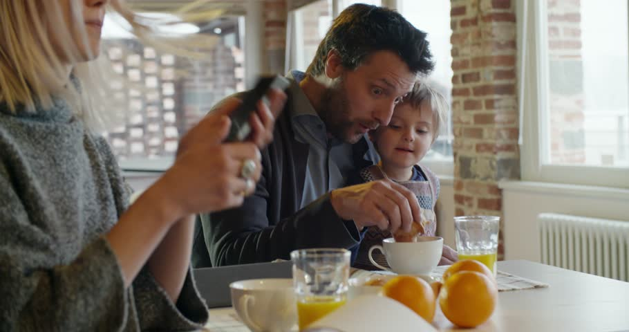 Modern family little girl having breakfast with dad while mom uses smartphone and works indoor in modern industrial house. caucasian. 4k handheld slow motion video shot