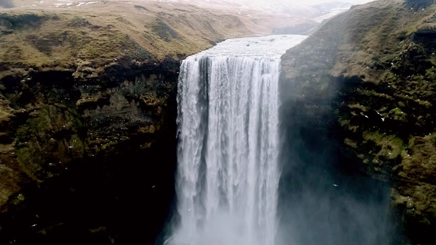 Aerial flight with drone over the famous  Skogar waterfall in Iceland. It is located on the South of the island. Image taken with action drone camera causing distortion and blur. Slow motion shot | Shutterstock HD Video #25673339