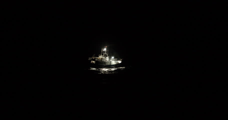 A lonely fishing boat sways around in rough waters in complete darkness. Only it's on-board lights are lighting the ship.