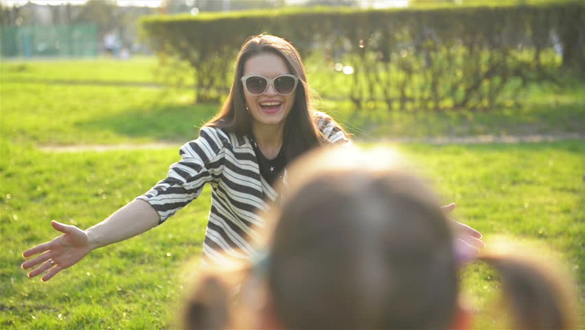 Young Mother with Long Hair and Sunglasses is Hugging her Daughter with Two Ponytails in the Park. Happy Family Enjoying Sunny Day Outdoors in Spring.