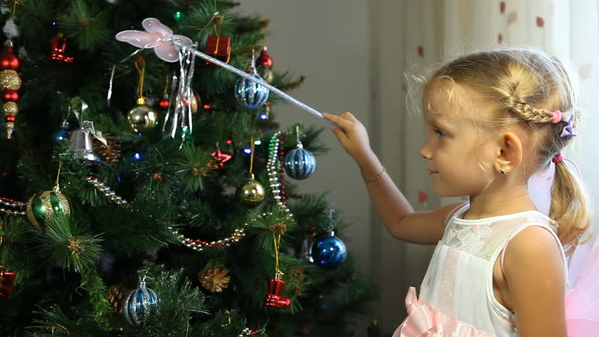Child Touching Playing With Her Magic Wand On The Christmas Tree