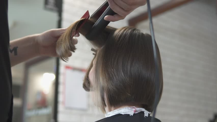 Close-up shot of a woman having her hair straightened in hair salon. Shot in slow motion.