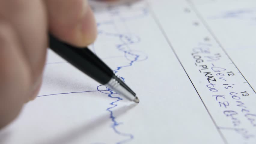 Close up of a man working with a graph, studying it and interpreting the data. Handheld real time close up shot | Shutterstock HD Video #25704689