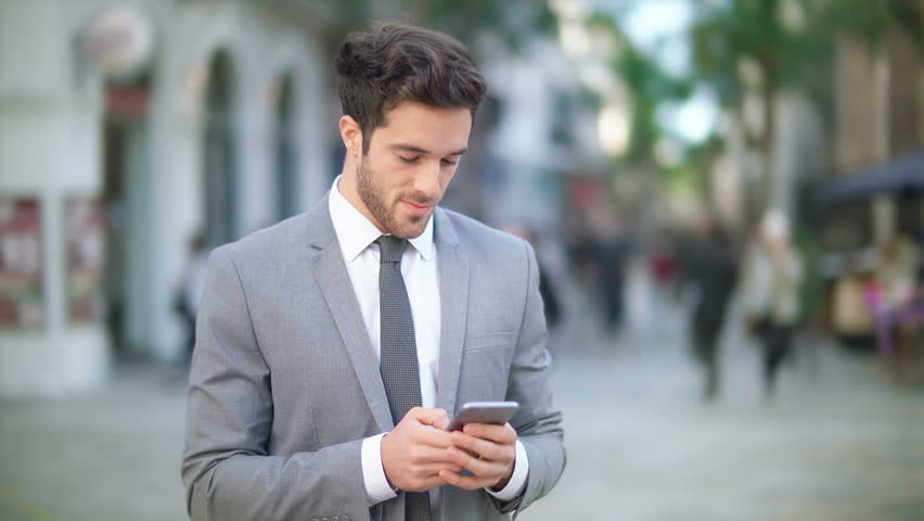 Handsome and young businessman using a cell phone in a crowded street. He is checking mails, chats or the news online. Technology. | Shutterstock HD Video #25718279