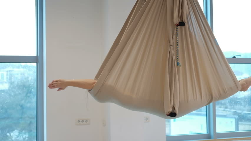 In a closed hammock for yoga in the air, a woman lies and rocks. She meditates in the unfolded canvas, which is attached to the ceiling. Beige matter in the form of a cocoon keeps the human body. The