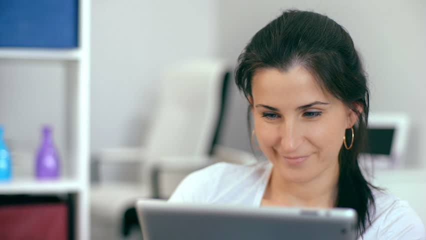 Beautiful woman using a digital tablet, while sitting on the couch at home | Shutterstock HD Video #25769549