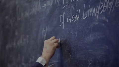 the hand writes on the blackboard a formula / the solution to the equation on the Board
