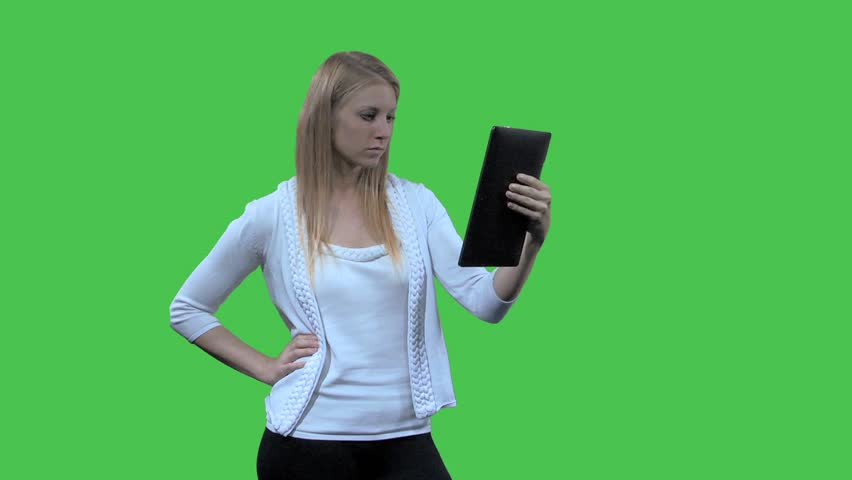 A young blond woman, standing, works with her tablet, happy with results | Shutterstock HD Video #2579069