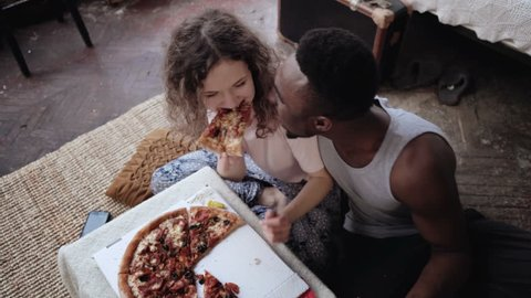 Woman offers pizza to man, but eat slice by herself. Multiracial couple having fun during the meal with fast food.