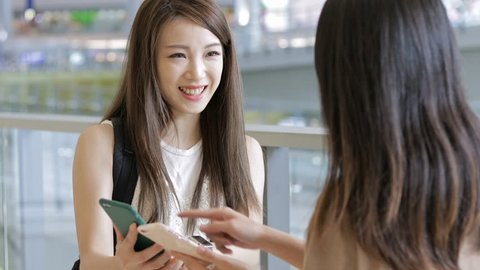 Young women discuss in cellphone in airport