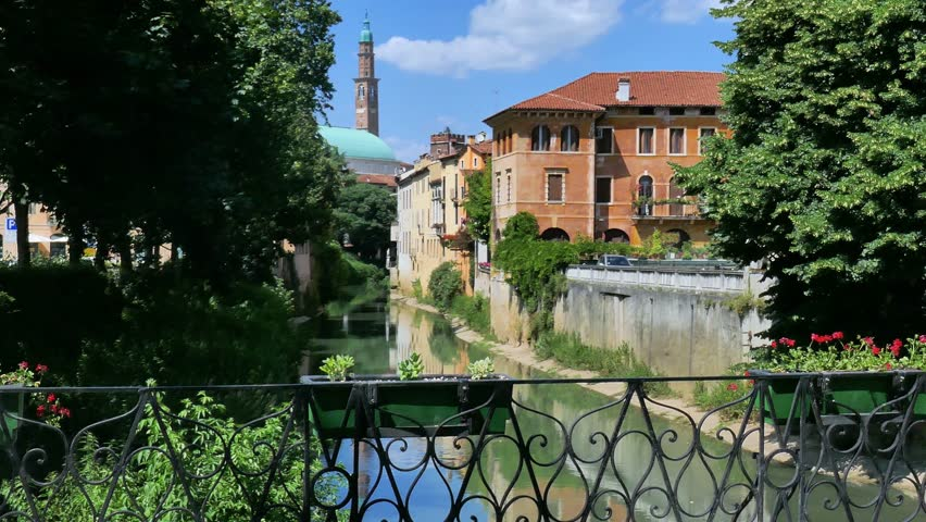 Vicenza - The Basilica Palladiana, designed by Andrea Palladio architect, and the Torre Bissara (tower) reflecting in the Retrone river in summer - Motion view