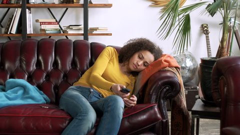 young african sad and lazy woman with curly hair and yellow blouse sit alone at home being bored and inactive, yawning and flipping TV channels during sunny day