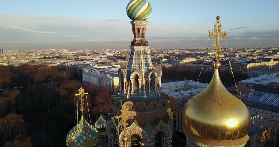 Aerial cinematic view (camera back): Flying from Dome of Church of the Savior on Blood at sunset. Early Spring cityscape of Saint Petersburg, Russia