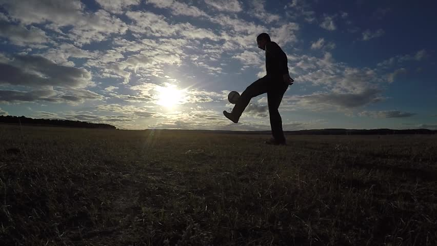 Soccer. Man is stuffing a football soccer ball sport silhouette at sunset football freestyle   Shutterstock HD Video #25842899