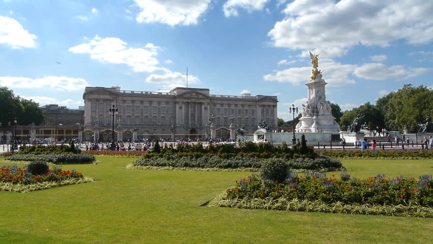 Buckingham Palace, London, England as seen from far away on a sunny day with a few clouds and green grass