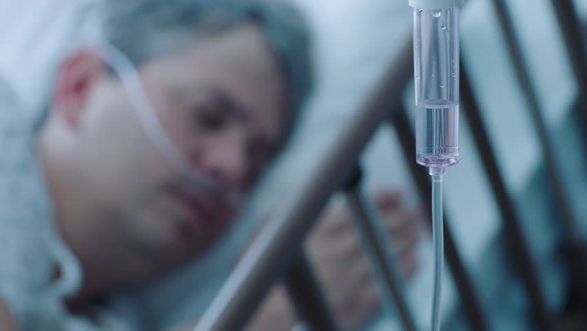 A sick middle aged man with an IV drip recovering in a hospital bed, slow motion, 4K