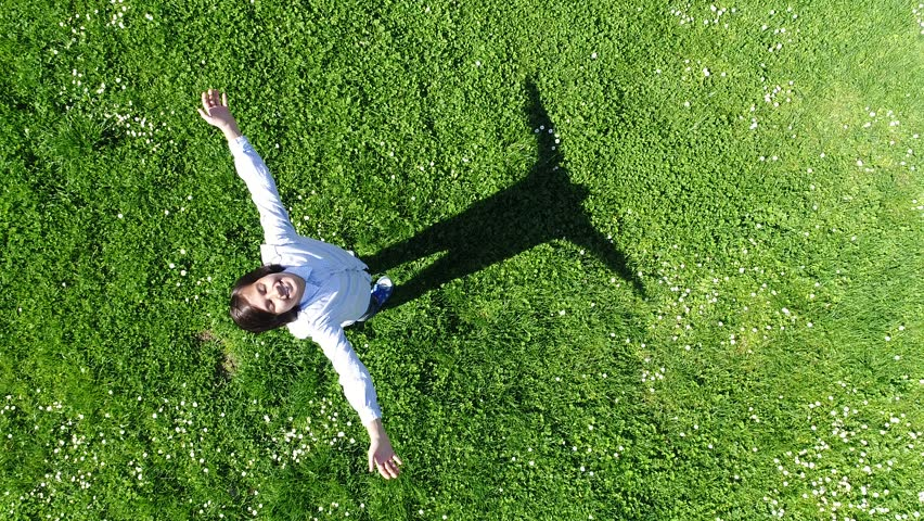 Aerial video view of a child standing on the park grass | Shutterstock HD Video #25919651