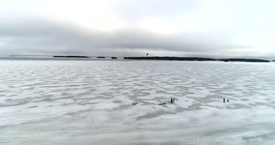 People walking on ice, Cinema 4k aerial view of people hiking on ice, infront Haukilahti coast, on a cloudy day, at the baltic sea, in Haukilahti, Espoo, Finland