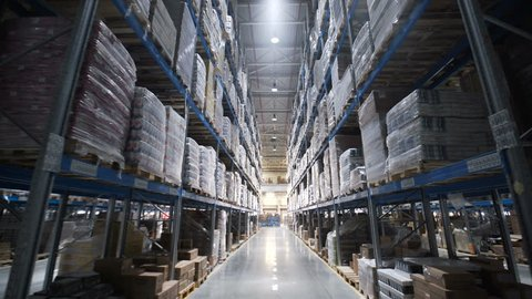 Warehouses large logistics commerce structure with boxes on the shelf. Teamwork male person industry production, using machine work and vehicle, delivering merchandise for transnational export indoors