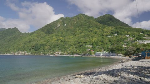 Wide panning shot of distant waterfront houses / Scotts Head, Dominica