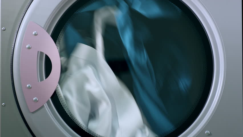 Drying laundry clothes. Close up of drying machine. Closeup of industry washing machine. Uniform turning in dryer machine. Dryer laundry machine. Laundry washing clothes