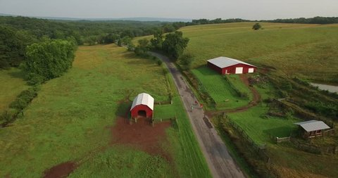 Aerial views of family bicycling along pastoral country roads.