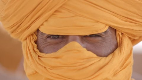 Portrait shot of a Arab male traditional looking serious into the camera. The male lives as nomad in the desert.