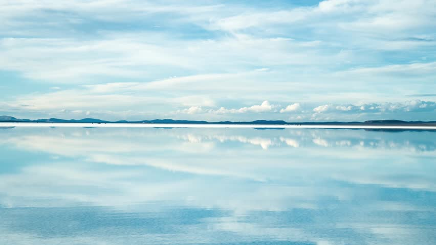 Time-lapse of the sunny day reflection of moving cloud and tourist moving around on the water in Salar de Uyuni, Bolivia, South America.