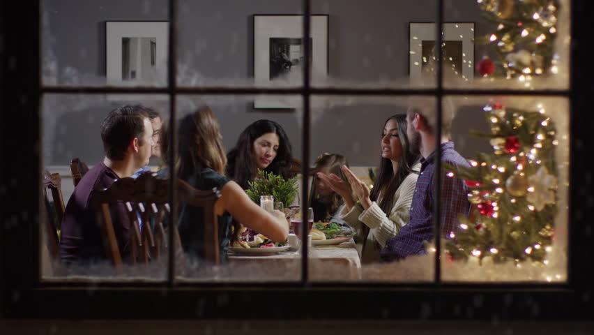 Medium zoom in shot of family talking at meal on Christmas behind window / Cedar Hills, Utah, United States