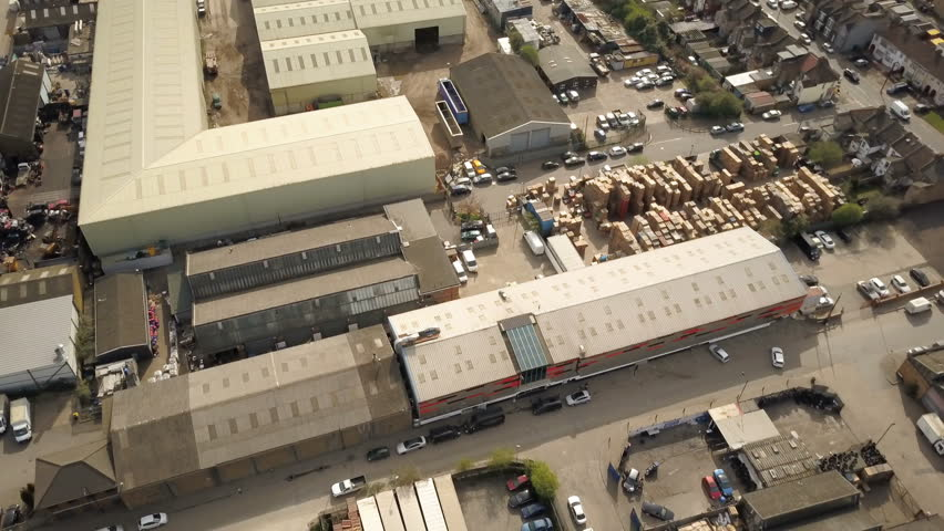 Industrial Estate: Warehouses and Factories. High Angled vertical drone reversing over a London industrial estate with factories and warehouses revealed, including a cement factory. #25999379