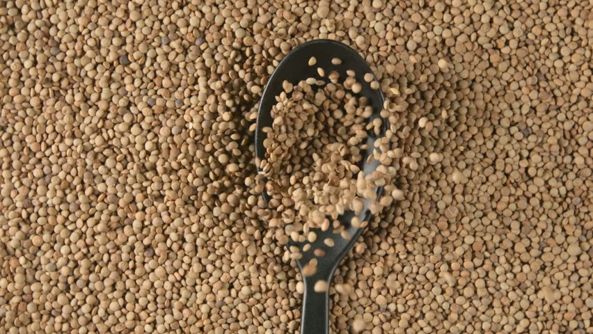 TOP VIEW: Spoon with lentils falls on a lentils (slow motion)