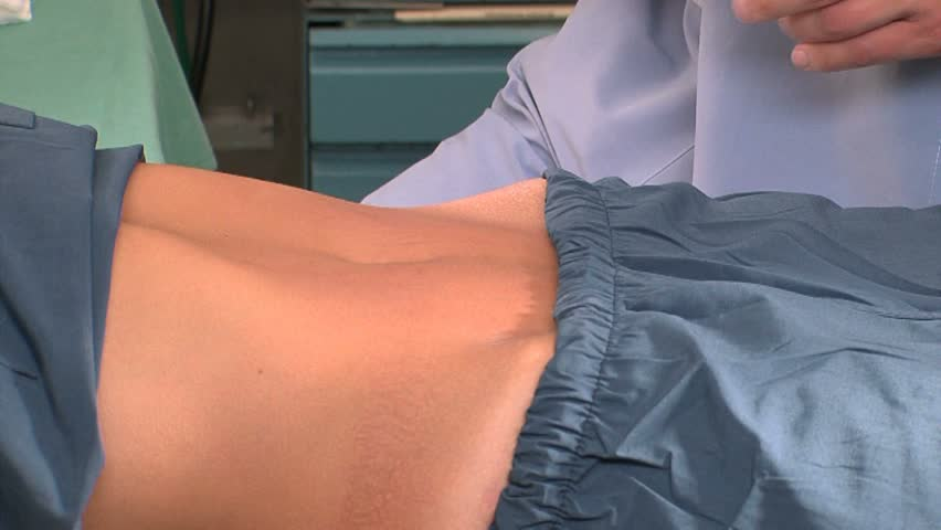 Plastic surgeon marks incision lines on stomach