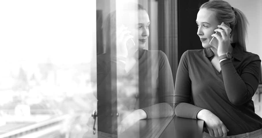 Elegant Woman Using Mobile Phone by window in office building | Shutterstock HD Video #26012339