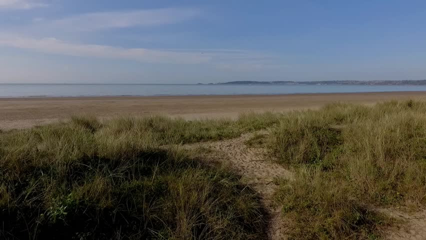 Looking from Swansea East over the sand dunes and dunegrass towards The Mumbles area of Swansea City, South Wales