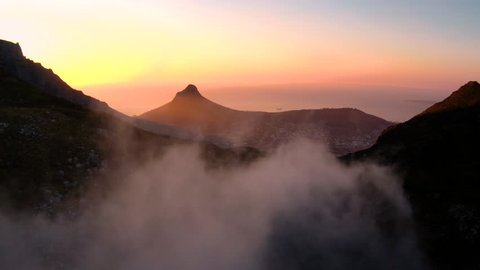 Drone reveal of Cape Town city during sunset with Lions Head and the ocean in the background.