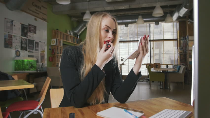 Business woman looking in the mirror and using lipstick at her worlplace in office, dolly shot