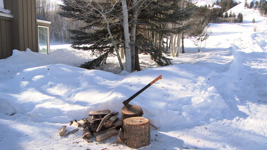 Man putting chopped wood into wheel barrel in the snow