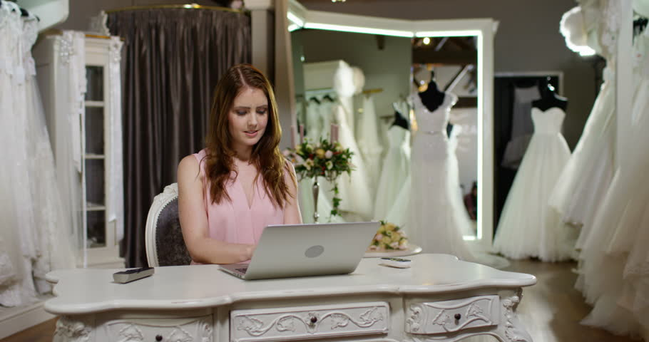 Young Wedding Dress Designer Working On Laptop In Her Shop