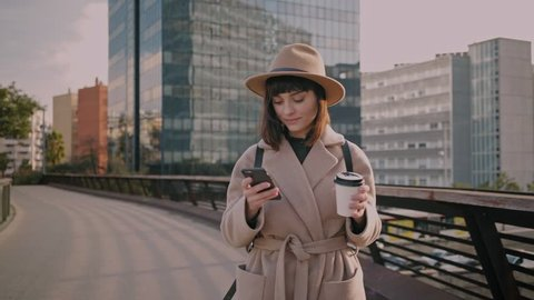 Hipster social media manager on her way to work, updates account on networks while world moves around in a fast pace.She sips on artisanal latte and smiles to warm morning sun