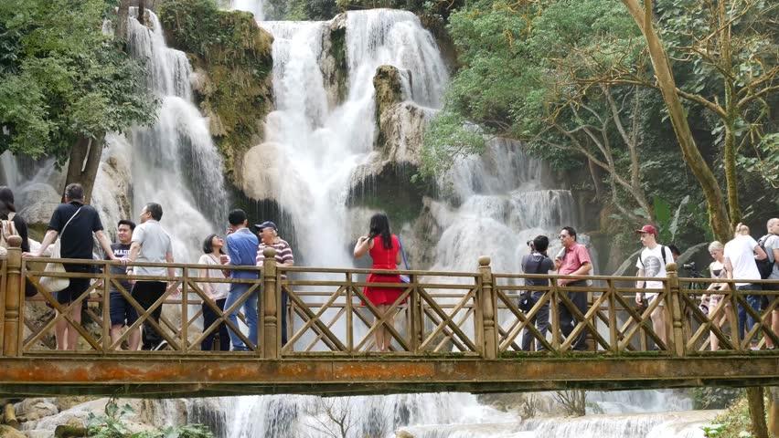 LUANG PRABANG, LAOS - NOV 24, 2016 Tourists at Kuang Si waterfall or Kuang Xi or Tat Kuang Si Falls, South of Luang Prabang.