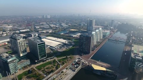 Panning aerial view of Media City and Salford Quays in Manchester, UK.