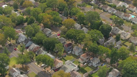 AERIAL: Flying above colorful rooftops of luxury suburban townhouses arranged in perfectly straight rows along beautiful tree avenue in lively American residential town on amazing sunny autumn day