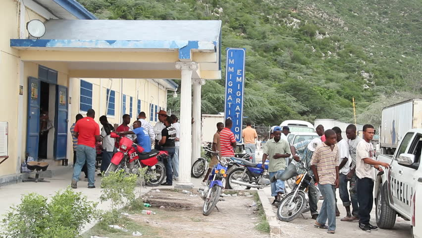 HAITI - JULY 2010:  A group of people stand outside an immigration office, and three men drive by sharing a motorcycle