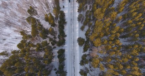 A shot from a height on an empty winter road in a picturesque area. Evergreen trees - Siberian spruce - surrounded by white snow. Winter day on a country road from a bird's eye view.
